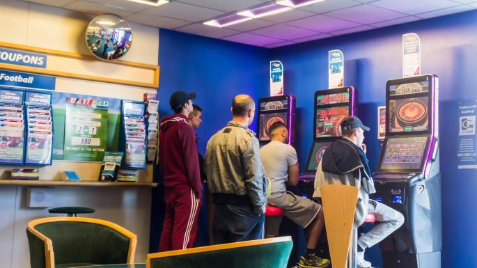 Men Playing On Fixed Odd Betting Terminals In Bookmaker