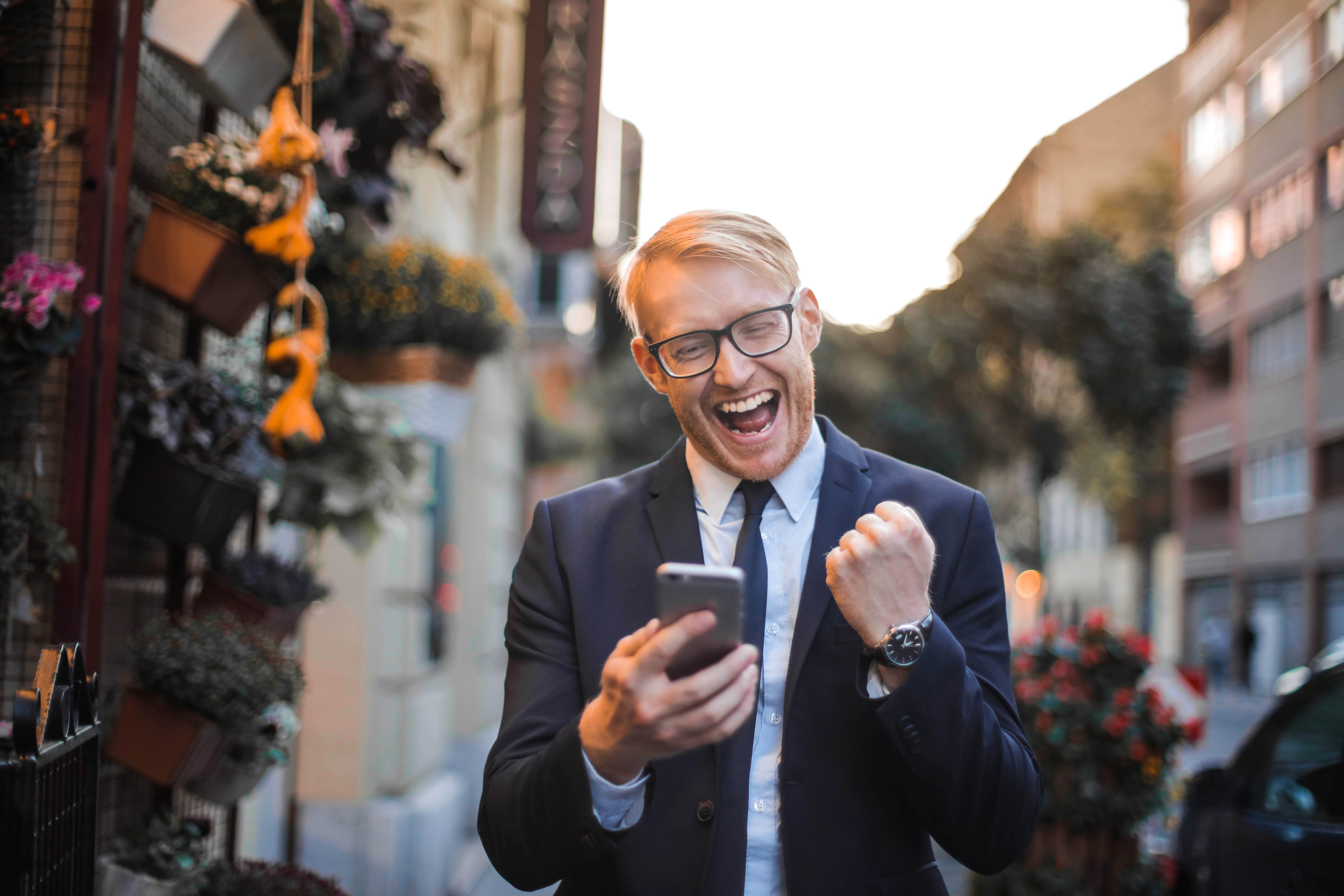 Man Holding Smartphone And Cheering