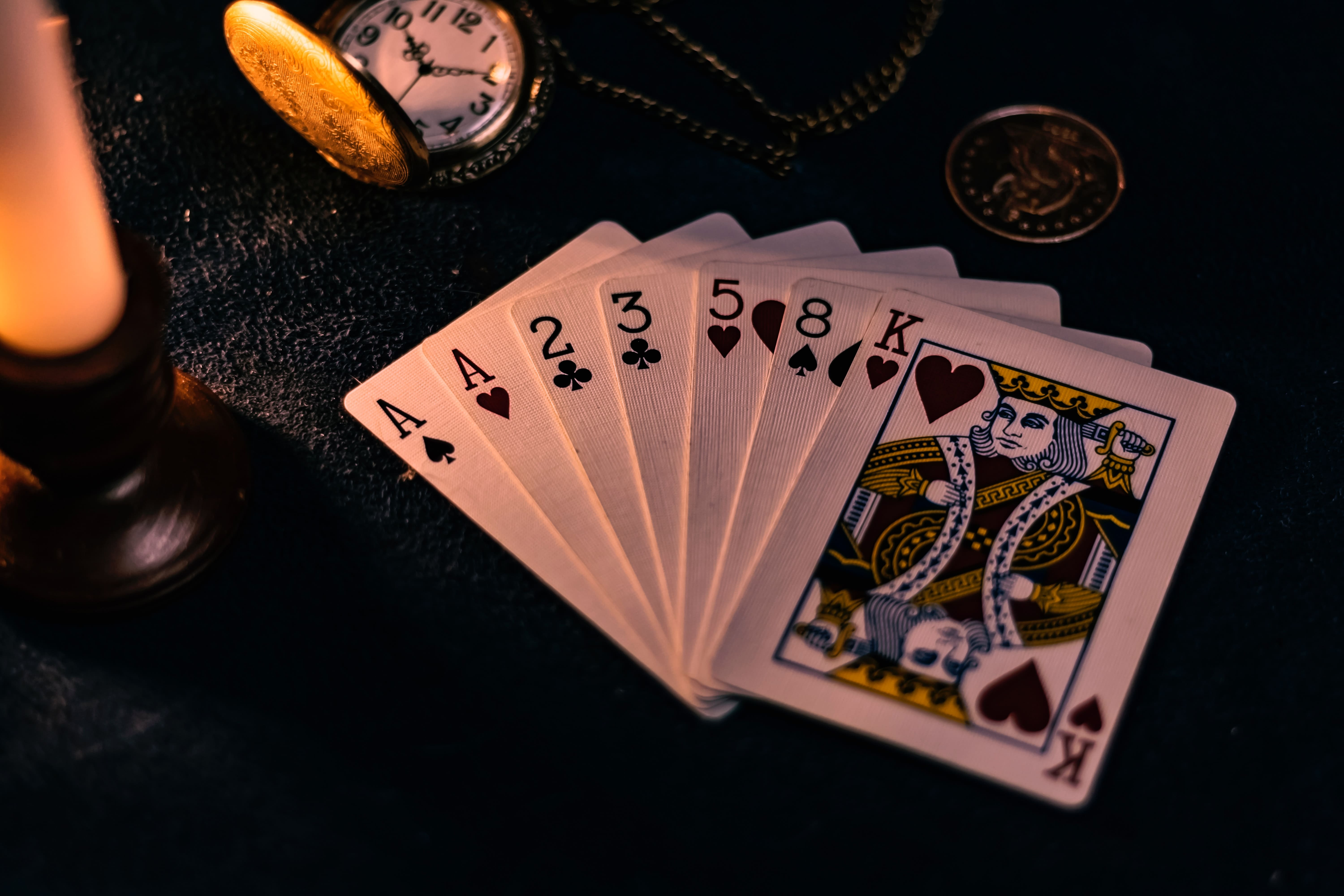 Spades And Clubs Playing Cards On Table With Pocketwatch